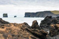 Atlantic Ocean stenig kust och sikt av Dyrholaey Royaltyfri Fotografi
