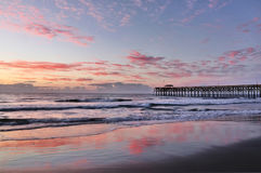 Atlantic ocean sunrise. Early morning at deserted Atlantic ocean beach. Marine landscape with wooden pier in South Carolina, Myrtle Beach area, USA. Long Stock Image