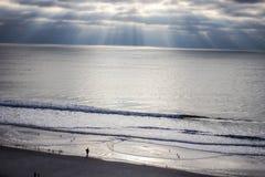 Atlantic Ocean Sunrise. Sunbeams illuminate  the Atlantic Ocean horizon with a single tourist in the foreground. Myrtle Beach, South Carolina Royalty Free Stock Images