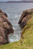 Atlantic Ocean water crashes in rock chasm, Inverasdale NW Scotl. Inverasdale, Scotland - June 9, 2012: Blue-green Atlantic Ocean water crashes in brown rock Royalty Free Stock Images