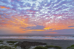 Atlantic Pastel Dawn. A cloudy and colorful pastel sky is reflected on the Atlantic Ocean with gently breaking waves on a Florida beach royalty free stock photos