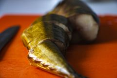 Atlantic smoked mackerel gutted without a head on a cutting board royalty free stock image