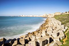 Atlantic Ocean shore and city center with Cathedral of Cadiz, An. Atlantic waves breaking on the urbanized shore of old Cadiz, Andalusia, Spain Royalty Free Stock Photography