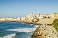 Atlantic Ocean shore and city center with Cathedral of Cadiz, An. Atlantic waves breaking on the urbanized shore of old Cadiz, Andalusia, Spain Stock Photography