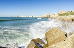 Atlantic waves crushing the waterbreaks in Cadiz, Andalusia, Spa. Atlantic waves breaking on the urbanized shore of old Cadiz, Andalusia, Spain Royalty Free Stock Photography