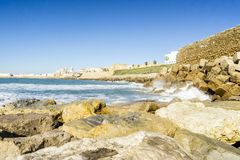 Atlantic waves crushing the waterbreaks in Cadiz, Andalusia, Spa. Atlantic waves breaking on the urbanized shore of old Cadiz, Andalusia, Spain Stock Photos