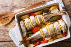Atlantische die kabeljauw met groenten in dichte omhooggaand van de bakselschotel wordt gebakken Ho stock foto