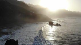 Atlantische golven op de achtergrond van bergen en zonsondergang op het Eiland Tenerife Canarische Eilanden en mooie aard Rotsen  stock video