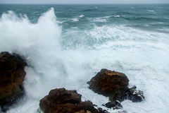 Atlantische Sturmwellen, die auf Felsen spritzen Stockfotografie