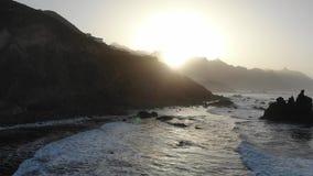 Atlantische Wellen auf dem Hintergrund von Bergen und von Sonnenuntergang auf der Insel von Teneriffa Kanarische Inseln und schön stock video