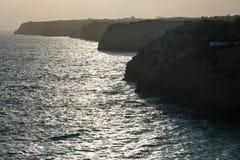 Atlantisk stenig kustlinje för aftonsolnedgång, Algarve, Portugal Royaltyfri Fotografi