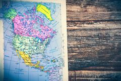 Atlas page North America continent retro map with wooden vintage background. Retro atlas page map of North America continent with a wooden vintage background in royalty free stock photo