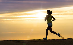 Atleet die bij zonsondergang op strand lopen Stock Foto