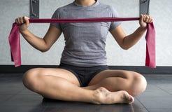 Atleet die een rode theraband houden aan oefening met royalty-vrije stock afbeelding