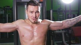 Atleet die geschiktheid opleiding op machine met gewichten in een gymnastiek doen stock videobeelden