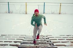 Atleet die met rode hoed en rode tennisschoenen de sneeuwtreden lanceren stock foto's