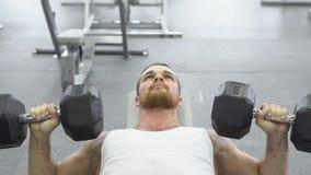 Atleet die oefening voor borst met domoren doen Jonge spiermensentreinen bij de gymnastiek Stock Fotografie