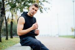 Atleet die op bank in park na het lopen met fles water rusten Rust een harde training stock afbeeldingen