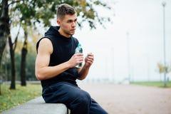 Atleet die op bank in park na het lopen met fles water rusten Rust een harde training royalty-vrije stock foto