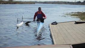 Atleet die op de rivier in een kano roeien Mens die de pijler naderen Het roeien, canoeing, het paddelen Opleiding kayaking Mens stock footage