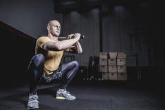 Atleet Doing Exercise With Clubbel bij de Gymnastiek Royalty-vrije Stock Foto