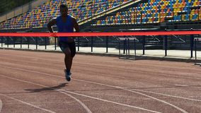Atleet het eindigen ras eerst en het afsnijden van rood lint, vierend overwinning stock footage