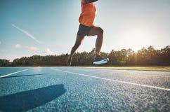 Atleet in medio lucht terwijl het sprinten onderaan een renbaan royalty-vrije stock foto's