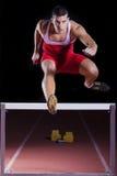 Atleet op hindernis op spoor en gebied royalty-vrije stock foto's