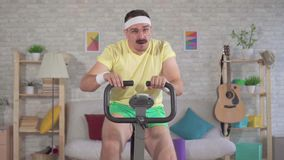 Atleet van de portret nam de grappige energieke mens van de jaren '80 met een snor thuis op hometrainer langzame mo in dienst stock video