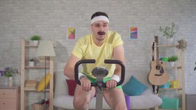 Atleet van de portret nam de grappige energieke mens van de jaren '80 met een snor thuis op een stationaire fiets in dienst stock videobeelden