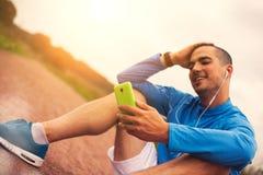 Atlet spojrzenia w smartphone po treningu Fotografia Stock