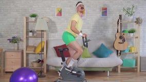 Atleta activo alegre del hombre a partir de los a?os 80 con un bigote dedicado en casa en una bicicleta est?tica MES lento almacen de metraje de vídeo