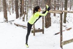 Atleta adatto della donna che fa la gamba del tendine del ginocchio che allunga gli esercizi all'aperto in legno Parco all'aperto Fotografia Stock Libera da Diritti