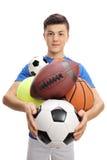 Atleta adolescente con los diferentes tipos de bolas de los deportes Foto de archivo