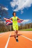 Atleta adolescente que corre con la bandera de Gran Bretaña Fotos de archivo libres de regalías