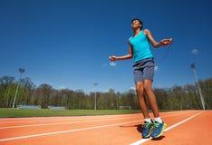 Atleta adolescente sonriente que salta la cuerda afuera Imagen de archivo libre de regalías