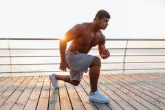Atleta africano dell'uomo che fa gli esercizi sul pilastro di mattina Immagine Stock Libera da Diritti