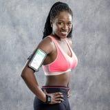 Atleta africano joven con los dispositivos digitales de la supervisión Foto de archivo libre de regalías