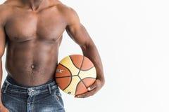 Atleta afro-americano muscular com a bola do basquetebol no fundo branco imagem de stock