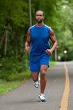 Atleta afro-americano Running On um trajeto arborizado Fotos de Stock