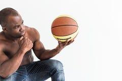 Atleta afroamericano muscular con la bola del baloncesto en el fondo blanco foto de archivo