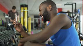 Atleta afroamericano sorridente che prende selfie nella palestra, tecnologie moderne archivi video