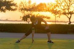 Atleta asiático da mulher do corredor saudável que estica os pés para aquecer-se antes de correr no parque no por do sol fotos de stock royalty free
