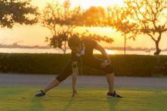 Atleta asiatico della donna del corridore sano che allunga le gambe per scaldarsi prima dell'correre nel parco sul tramonto fotografie stock libere da diritti