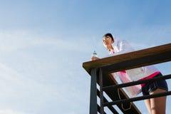 Atleta asiatico femminile motivato che riposa dopo l'allenamento urbano Fotografia Stock
