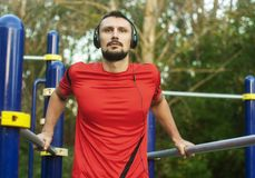 Atleta atractivo joven del hombre que ejercita el exterior del empuje para arriba foto de archivo