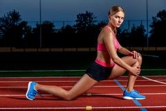Atleta attraente della giovane donna che allunga le gambe sullo stadio Fotografie Stock