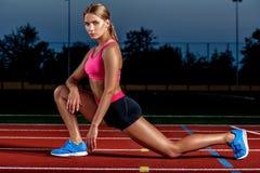 Atleta attraente della giovane donna che allunga le gambe sullo stadio Immagini Stock Libere da Diritti