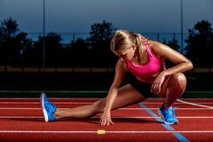 Atleta attraente della giovane donna che allunga le gambe sullo stadio Fotografia Stock Libera da Diritti