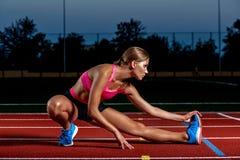 Atleta attraente della giovane donna che allunga le gambe sullo stadio Immagine Stock Libera da Diritti